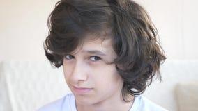 Muchacho rizado-cabelludo lindo que el adolescente mira en la c?mara que r?e y que hace una expresi?n facial divertida 4k, c?mara almacen de video