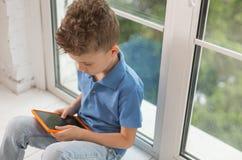 Muchacho rizado en el polo que juega a juegos en el ordenador portátil Imagen de archivo libre de regalías