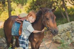 Muchacho rojo lindo del pelo que sonríe a la cámara y a la situación en bosque con el caballo Foto de archivo