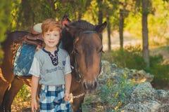Muchacho rojo lindo del pelo que sonríe a la cámara y a la situación en bosque con el caballo Imagen de archivo