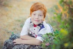Muchacho rojo lindo del pelo que sonríe a la cámara y a la situación en bosque con el caballo Fotografía de archivo libre de regalías