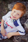 Muchacho rojo lindo del pelo que sonríe a la cámara y a la situación en bosque con el caballo Imagenes de archivo