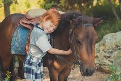 Muchacho rojo lindo del pelo que sonríe a la cámara y a la situación en bosque con el caballo Imagen de archivo libre de regalías