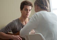 Muchacho romántico que toca la guitarra para su novia Imágenes de archivo libres de regalías