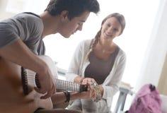 Muchacho romántico que toca la guitarra para su novia Foto de archivo