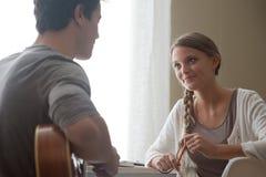 Muchacho romántico que toca la guitarra para su novia Imagen de archivo libre de regalías
