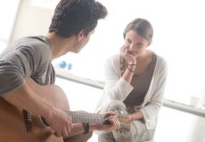 Muchacho romántico que toca la guitarra para su novia Fotos de archivo libres de regalías