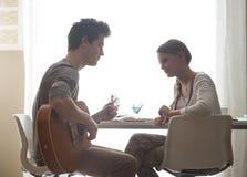 Muchacho romántico que toca la guitarra para su novia Foto de archivo libre de regalías
