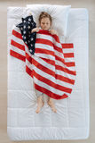Muchacho rubio agradable que es cubierto con la bandera de los E.E.U.U. Fotografía de archivo