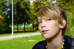 Muchacho rubio atractivo en parque Imagen de archivo libre de regalías