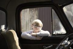 Muchacho rubio con los vidrios que miran a través de ventana vieja del camión Fotos de archivo
