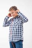 Muchacho rubio del cantante emocional en una camisa de tela escocesa con los auriculares Foto de archivo libre de regalías