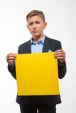 Muchacho rubio emocional del adolescente en un traje con una hoja de papel amarilla para las notas Imagen de archivo