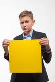 Muchacho rubio emocional del adolescente en un traje con una hoja de papel amarilla para las notas Foto de archivo libre de regalías