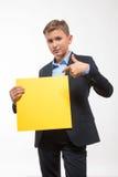 Muchacho rubio emocional del adolescente en un traje con una hoja de papel amarilla para las notas Fotografía de archivo libre de regalías