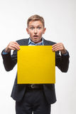 Muchacho rubio emocional del adolescente en un traje con una hoja de papel amarilla para las notas Imagen de archivo libre de regalías