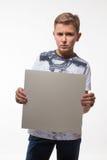 Muchacho rubio emocional en una camisa blanca con una hoja de papel gris para las notas Imagen de archivo