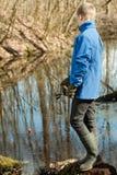 Muchacho rubio en la pesca de la chaqueta azul y de los guantes Foto de archivo