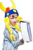 Muchacho rubio enojado lindo en una camisa elegante que sostiene un libro azul muy grande que parece peligroso Imagen de archivo