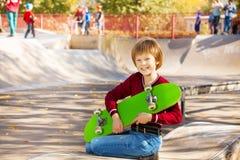 Muchacho rubio feliz con la sentada verde del monopatín Imagen de archivo libre de regalías