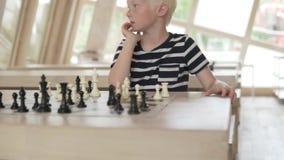 Muchacho rubio hermoso que juega a ajedrez almacen de metraje de vídeo