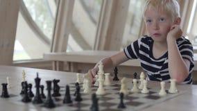 Muchacho rubio hermoso que juega a ajedrez metrajes