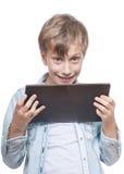 Muchacho rubio lindo en una camisa azul que sostiene una PC de la tableta Fotografía de archivo libre de regalías