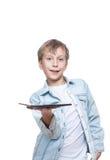 Muchacho rubio lindo en una camisa azul que sostiene una PC de la tableta Imagen de archivo libre de regalías