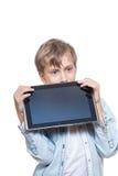 Muchacho rubio lindo en una camisa azul que sostiene una PC de la tableta que parece enojada Fotos de archivo libres de regalías