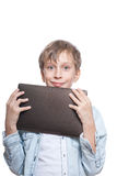 Muchacho rubio lindo en una camisa azul que sostiene una PC de la tableta que parece sorprendida Imágenes de archivo libres de regalías