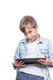 Muchacho rubio lindo en una camisa azul que sostiene una PC marrón de la tableta Imagen de archivo