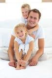 Muchacho rubio lindo que abraza a su papá que se sienta en una cama