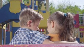 Muchacho rubio lindo y una muchacha bonita que se sienta en el banco delante del abrazo del patio Un par de niños felices almacen de video