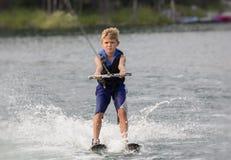 Muchacho rubio que aprende al waterski en un lago Imagen de archivo