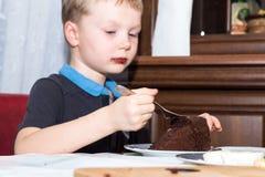 Muchacho rubio que come la torta de chocolate en la placa en la tabla con la bifurcación Fotos de archivo libres de regalías