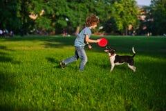 Muchacho rubio que juega con su perro blanco y negro en el césped en el parque Fotos de archivo libres de regalías
