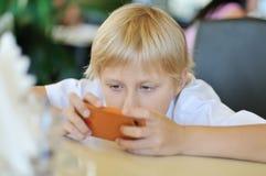 Muchacho que juega el teléfono Fotografía de archivo libre de regalías