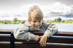 Muchacho rubio sonriente en un banco en el parque Foto de archivo libre de regalías