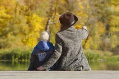 Muchacho rubio y su madre que se sientan en el muelle Día del otoño v trasero Imagen de archivo libre de regalías