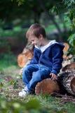 Muchacho, sentándose en los troncos de un árbol, jugando con el aeroplano de madera Fotos de archivo