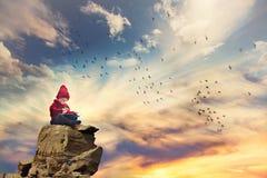 Muchacho, sentándose en una roca en el cielo, pájaros que vuelan alrededor de él Foto de archivo libre de regalías