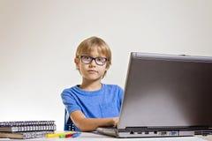 Muchacho serio concentrado con los vidrios usando el ordenador portátil mientras que se sienta en el escritorio en casa Tecnologí Fotografía de archivo libre de regalías