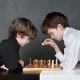 Muchacho serio dos que juega al ajedrez, estudio Imágenes de archivo libres de regalías
