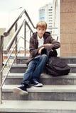 Muchacho serio que se sienta en las escaleras. al aire libre Foto de archivo libre de regalías