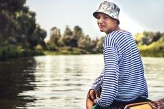Muchacho simple hermoso del adolescente que viaja en barco en el río durante días de fiesta del campamento de verano del campo Fotos de archivo