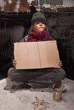 Muchacho sin hogar joven en la calle con una muestra fotografía de archivo