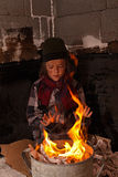 Muchacho sin hogar sucio que se calienta en el fuego imágenes de archivo libres de regalías