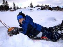 Muchacho sledding en la nieve Fotografía de archivo