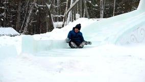 Muchacho sledging abajo de la colina en el parque del invierno almacen de metraje de vídeo