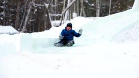 Muchacho sledging abajo de la colina en el parque del invierno almacen de video
